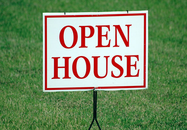 An 'Open House' sign against green grass.